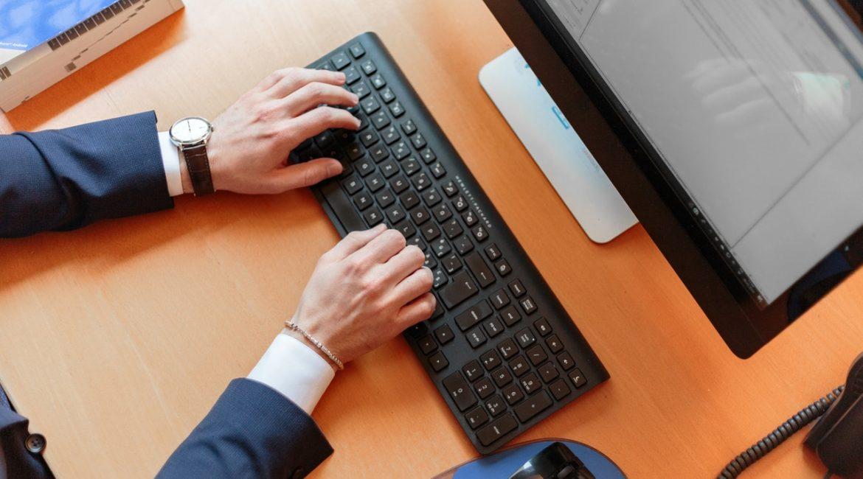 Person arbejder på en stor computer på kontor