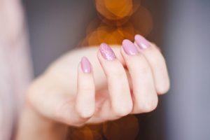 Dame har pink negle med glimmer på